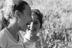 Two Happy little girls laughing and hugging at the summer park. Happy chidhood concept. Black and white photo royalty free stock images