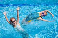 Two happy little girls playing  in the swimming pool Royalty Free Stock Images