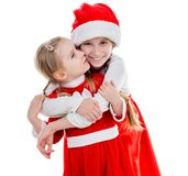 Two happy little girls in santa suits embracing Royalty Free Stock Images