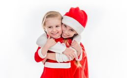Two happy little girls in santa suits embracing Stock Photos