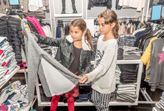 Two happy  little girls shopping in retail store Royalty Free Stock Photography