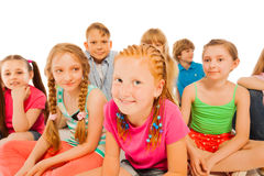Two happy little girls sit in group of friends Stock Photos