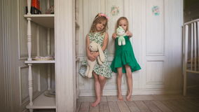 Two happy little girls are standing in the bright room in the house. stock video