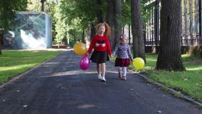 Two happy little girls walk with balloons in green summer park stock footage