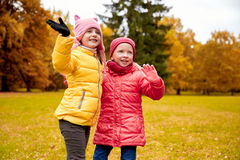 Two happy little girls waving hand in autumn park Stock Photography