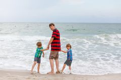 Two little kids boys and father on the beach of ocean stock images
