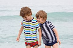 Two happy little kids boys running on the beach of ocean. Funny children, siblings, twins and best friends making. Vacations and enjoying summer on stormy rainy royalty free stock image