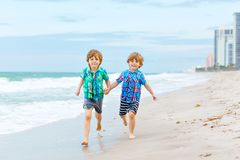 Two happy little kids boys running on the beach of ocean. Funny cute children, sibling and best friends making vacations royalty free stock images