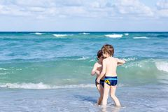 Two kid boys running on ocean beach. Little children having fun. Two happy little kids boys running on the beach of ocean. Funny cute children, siblings, twins stock photography