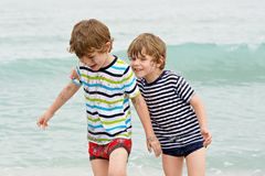 Two happy little kids boys running on the beach of ocean stock photos