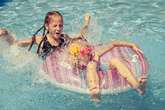 Two happy little kids playing  in the swimming pool Stock Photos