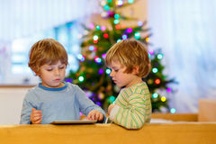 Two happy little kids playing with tablet pc Royalty Free Stock Photos