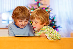Two happy little kids playing with tablet pc Royalty Free Stock Images