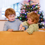 Two happy little kids playing with tablet pc, indoors Stock Photo