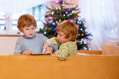Two happy little kids playing with tablet pc, indoors Stock Images