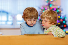 Two happy little kids playing with tablet pc, indoors Stock Photography
