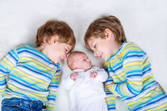 Two happy little preschool kids boys with newborn baby girl royalty free stock image