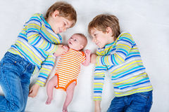 Two happy little preschool kids boys with newborn baby girl Stock Images