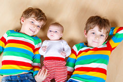 Two happy little preschool kids boys with newborn baby girl Royalty Free Stock Images