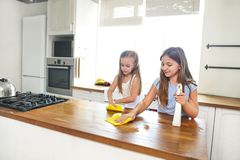 Two happy  little sisters cleaning kitchen table stock photos