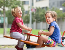Two happy little sisters on teetering board Stock Photos