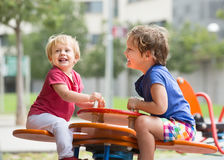 Two happy little sisters on teetering board Royalty Free Stock Photos