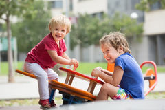 Two happy little sisters on teetering board Royalty Free Stock Images