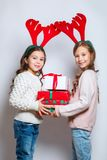 Two happy little smiling girls with christmas gift boxs. Merry christmas and happy new year . Two happy little smiling girls with christmas gift boxs Royalty Free Stock Photography
