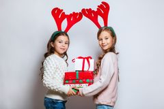 Two happy little smiling girls with christmas gift boxs. Merry christmas and happy new year . Two happy little smiling girls with christmas gift boxs Stock Photo