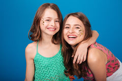 Two happy lovely sisters with decorations on cheeks laughing Royalty Free Stock Photo