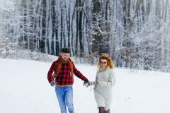 Two happy lovers are holding hands and cheerfully running along the snowy forest during the snowfall. Royalty Free Stock Photography