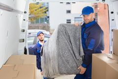 Two Movers Unloading Furniture From Truck
