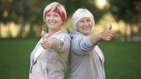 Two happy mature women smiling and showing thumbs up in park, healthy lifestyle stock image