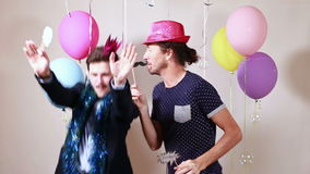 Two happy men dancing with props in photo booth stock video footage