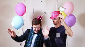 Two happy men dancing with props in photo booth. Two smiling happy men dancing with props in photo booth stock footage