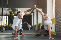 Two happy men fitness workout together at gym. Multiethnic happy men workout in fitness club. Cheerful african-american and caucasian guys making couple plank or royalty free stock photo