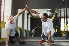 Two happy men fitness workout together at gym. Multiethnic happy men workout in fitness club. Cheerful african-american and caucasian guys making couple plank or royalty free stock image