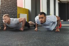 Two happy men fitness workout together at gym. Multiethnic happy men workout in fitness club. Cheerful african-american and caucasian guys making couple plank or royalty free stock photography