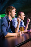 Two happy men raising their fist while having beer at bar counter Stock Photos