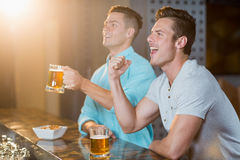 Two happy men raising their fist while having beer at bar counter Stock Image