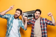 Two happy men in shirts listening music by record player. While screaming and looking at the camera over yellow background Royalty Free Stock Photo