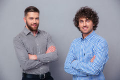Two happy men standing with arms folded. Portrait of a two happy men standing with arms folded on gray background stock images