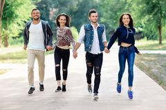 Two happy men and women running holding hands in park. Two happy men and women running holding hands in summer park. Attractive men and women company walking Stock Photography