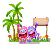Two happy monsters near the empty wooden signboard beside the pa Royalty Free Stock Photo