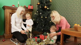 Two Happy Mothers With Babies Playing With. Two happy young mothers with adorable babies toddlers playing with Christmas tree decorations on the floor while stock video footage