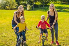 Two happy mothers teach their happy sons to ride a bike stock photo