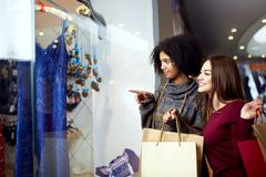 Two happy multiethnic young mixed race woman shopping for lingerie near clothing boutique shop window, decide whether to royalty free stock photography