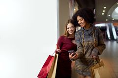 Two happy multiethnic young mixed race woman shopping for lingerie near white shop window copyspace, looking at stock images