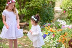 Two little girls in white dresses having fun a summer garden. royalty free stock image