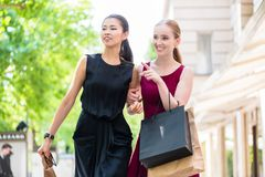 Two happy multiracial women out shopping. Together standing in an urban street pointing and smiling with bags over their arms Stock Photography